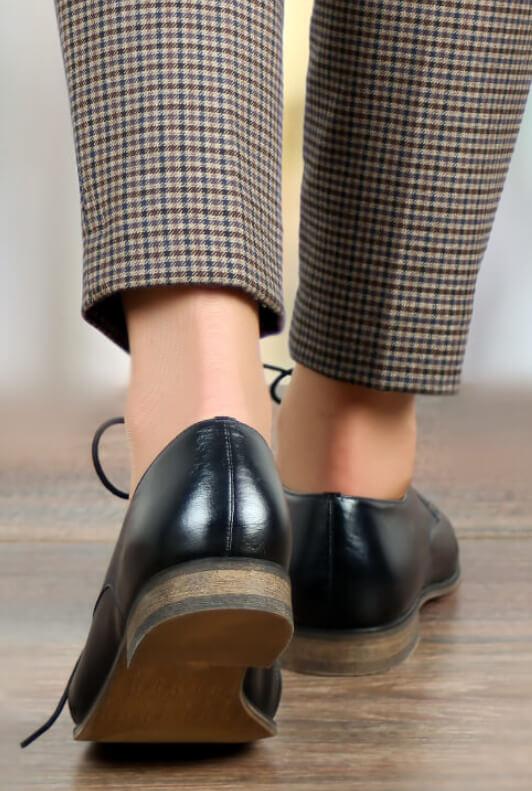Donna con scarpe per l'ufficio stringate nere e pantaloni a quadretti